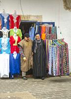 two men in tradidional dress coming out of a shop, Essaouira, Morocco.