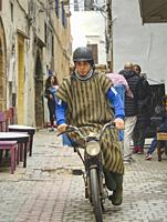 young man in traditional dress on a moped, Essaouira, Morocco.