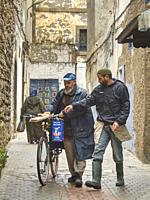 man with some lumber on his bicycle with a friend, Essaouira, Morocco.