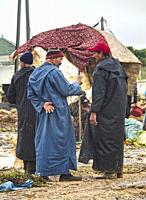 two men in tradidional dress talking at the market in Ida Ougourd Market, near Essaouira, Morocco.