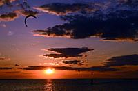 A thrill seeker rides his surf kite across a bay as the sun sets.
