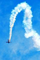 A stunt pilot makes an arching descent at an air show.