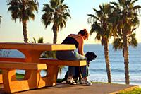 An adult woman enjoys a moment wth her dog at a picnic table with a view of the Pacific Ocean.