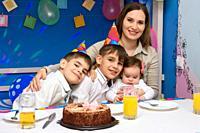 Happy family hugs mom at birthday party.