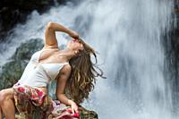 Woman lying on the rock by the river wearing a white swimsuit