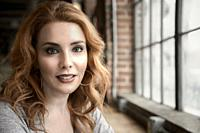 A portrait of a pretty 37 year old redheaded woman smiling directly at the camera.