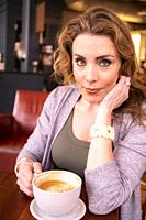 A pretty 37 year old redhead woman in a holding a large cup of coffee in a cafe.