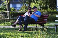older couple, on bench, inspecting pics, images, on smartphone