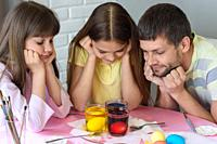 Dad and two daughters are watching how the eggs are painted in glasses with dyes.