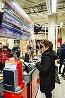 Stockholm, Sweden April 1, 2020 Shoppers inside a supermarket in Liljeholmen stand behind plexiglas protection at the cashier.