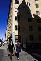 Stockholm, Sweden April 1, 2020 Pedestrians on the corner of Timmermansgatan and Bengt Ekehjelmsgatan on Sodermalm and the shadow of a classic buildin...
