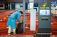 Singapore, Republic of Singapore, Asia - A passenger at Changi Airport's Terminal 1 wears a protective face mask and a raincoat to prevent an infectio...