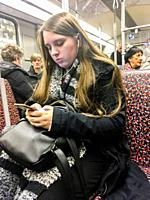 Berlin, Germany. Young, teenage girl concentrated on her smartphone, while taking a subway ride underneath the city of Berlin.