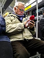 Berlin, Germany. Elder man concentrated on his smartphone, while taking a subway ride underneath the city of Berlin.
