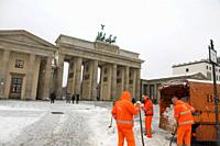 Berlin Brandenburg gate snowing with street cleaners Germany.