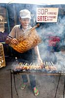 An Indonesian Man Cooking/Grilling Meat In The Street, Jakarta, Indonesia.