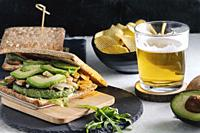 Vegan homemade spinach sandwich with avocado, onion, and arugula. Beer and chips in background. Healthy fast food concept.