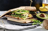 Spinach green burger in sandwich with fresh avocado, mushrooms, grilled onion and arugula, on a wooden cutting board.