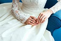 dress up the bride in a wedding dress with corset and lacing.