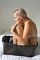 A naked woman sits in a plastic basket on the bed in the autumn in Canada.