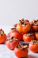 Some persimmons in a plate on a marble surface. Front vertical shot.