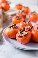Detail close up of persimmons fresh from the garden. Natural light.