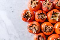 A group of fresh persimmons over a marble surface. Overhead flat lay shot.