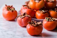 Close up of persimmons over a marble surface. Front shot.