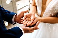 groom puts bride on wedding ring.