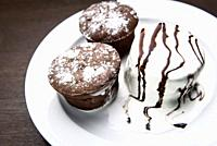 chocolate muffins with ice cream drizzled with chocolate topping.