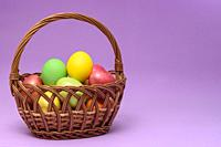Basket with easter eggs on a dark pink background.