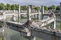 cityscape with flooded ruins of collapsed concrete building framework with Black-billed gulls on wrecked pillars and warped reinforcing steel, shot in...