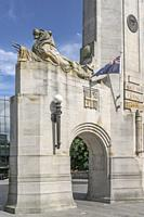 cityscape with sculpture and flag at monumental Remebrance Bridge arch, shot in bright spring light at Christchurch, South Island, New Zealand.