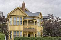 cityscape with traditional wooden Victorian two-storey house, shot in bright spring cloudy light at Christchurch, South Island, New Zealand.