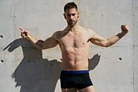 Portrait of a pretty guy dressed in boxers on a concrete wall.