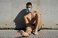 Portrait of a gorgeous guy wearing a mask to avoid infection. Coronavirus concept.