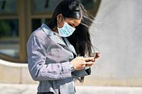 Girl with a mask to avoid contagion walking down the street. Coronavirus concept.