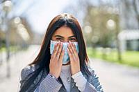 Girl putting on a protective mask to avoid contagion while walking down the street. Coronavirus concept.