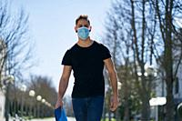Caucasian male in medical masks walking in a city park. The concept of Coronavirus.