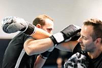 young man fighter, training kick boxing with his trainer, fighting in the ring .