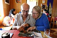 A couple looks at a map in a mountain refuge in the Dolomites, Italy.