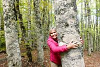 Woman hugging a tree in the beech tree forest near Mormanno, Calabria, Italy..
