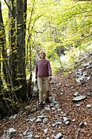 A woman in a beech tree forest near Mormanno, Calabria, Italy.