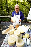 A man sells cheese at the roadside in the forest near Mormanno, Calabria, Italy.