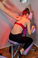 Back pain. Infrared heat light lamp therapy to a girl in a massage chair with red bra and sport trousers.