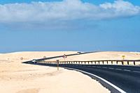 Scenic view of road through sand dunes against sky. Corralejo, Fuerteventura, Canary Islands.