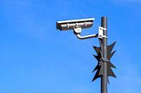 Surveillance camera against bright blue sky.