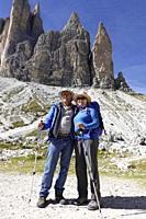 A couple of hikers beneath the peaks of Drei Zinnen, in the Dolomies, Italy.