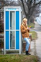 A woman leaning on a phone booth checks her smart phone , Lancaster, Pennsylvania, USA.