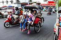 A Group Of Indonesian Children Travelling In A Traditional Becak (Cycle Rickshaw), Malioboro Street, Yogyakarta, Indonesia.